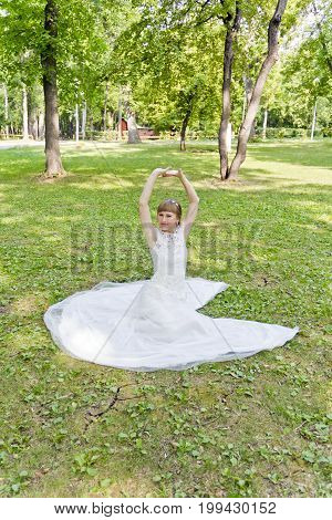 Bride in white lace dress with upwards hands sitting on the grass