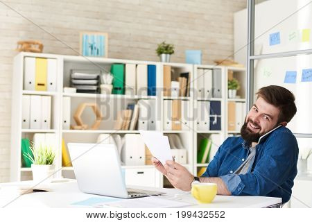 Portrait of modern bearded businessman in casual wear smiling happily to camera while speaking by phone at work in modern office