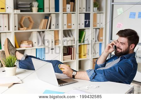 Portrait of modern bearded businessman in casual wear smiling happily while speaking by phone at break  in modern office