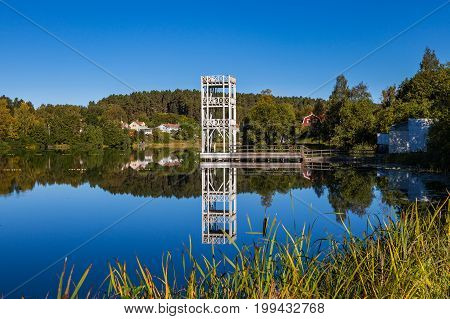 A jumping tower and traditional cottages stands by the lakeside in Hedemora, Sweden