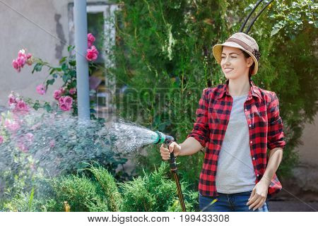 happy young woman gardener watering garden with hose. People, gardening, care of flowers, hobby concept