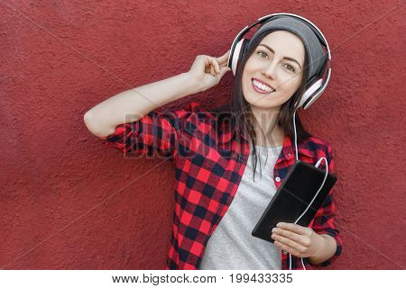young woman with tablet computer listening music in headphones. Girl using digital tablet outdoors. Copy space. Technology, music, lifestyle, and millenial people concept