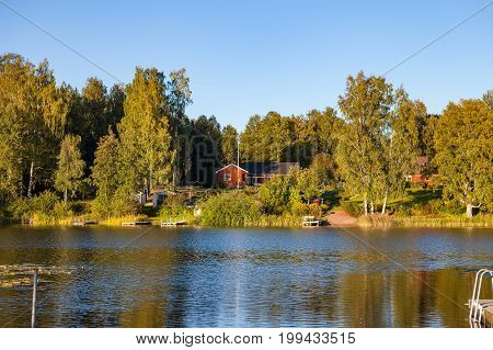 A traditional cottage stands by the lakeside in Hedemora, Sweden