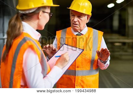 Portrait of senior plant manager talking to young assistant writing down instructions,  both wearing hardhats and reflective jackets