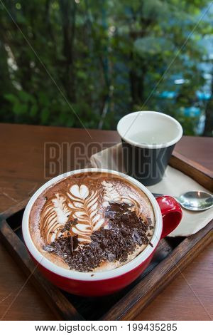 a cup of hot mocha coffee with chocolate and a cup of water green nature as background