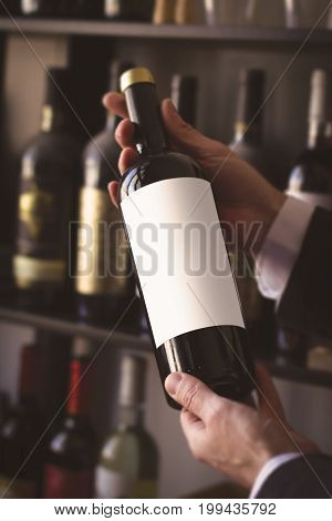 close up of hands of Caucasian men with white shirt holding a red wine bottle with white blank label against the sale shelves of a wine store or restaurant in natural light