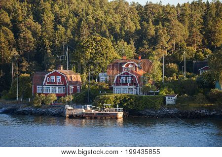 View on luxury cottages with private pier along Stockholm archipelago, Sweden. Summer sunset time.