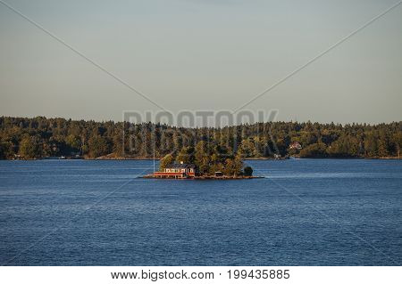 View on lonely island in Stockholm archipelago, Sweden. Private hut and pier. Summer sunset time.