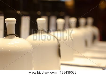 perspective view of white ceramic fragrance bells in niche perfume store selective focus