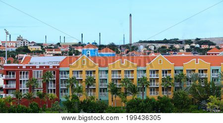 Colorful Resort with Oil Refinery in Background on Curacao