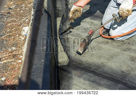 worker while burning the waterproof membrane on a roof
