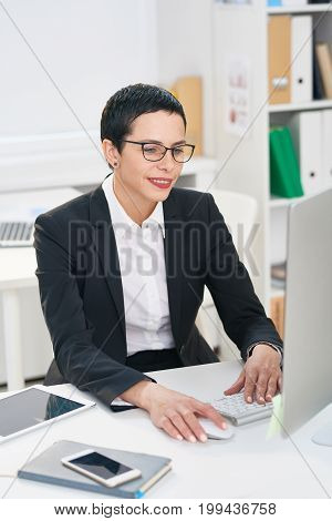 Waist-up portrait of beautiful middle-aged entrepreneur in eyeglasses checking business emails while sitting at desk in modern office