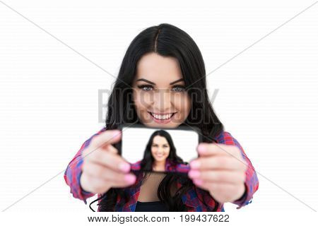Girl In A Plaid Shirt Makes Selfie. Portrait Of A Smiling Woman Making Selfie Photo On Smartphone Is