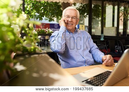 Portrait of senior man speaking by phone smiling happily while working with laptop in outdoor cafe lounge during coffee break