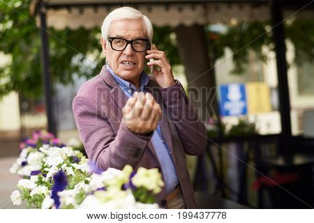Portrait of modern senior man speaking by phone outdoors in streets of city, leaning on flowerbed