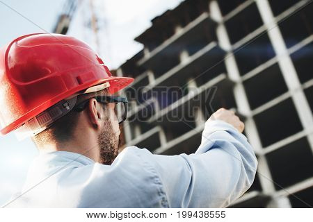Architect Or Safety Officer In Red Hard Hat On Background Of Construction Site. Engineer Builder Man