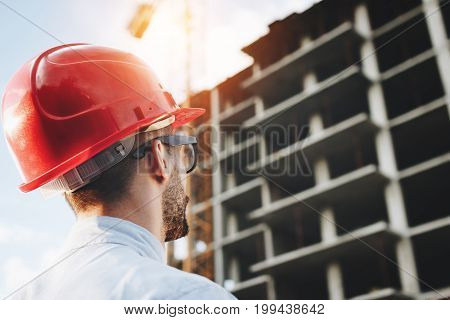 Young Engineer In Red Helmet Inspects Construction Of Building. Bearded Businessman On Background Of