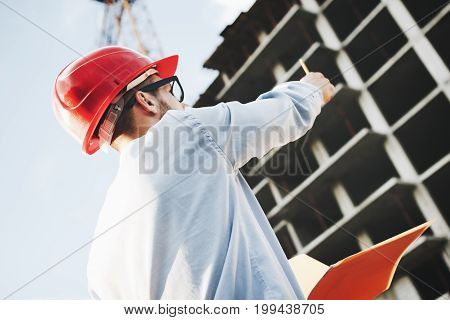 Young Businessman In Hard Hat With Pencil In Hand On Construction Site. Portrait Of Architect Or Eng