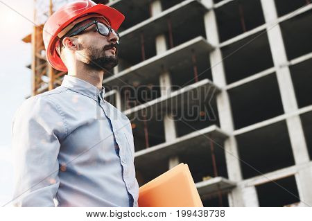 Young Bearded Businessman Or Engineer Wearing Glasses And Helmet On Construction Site. Portrait Of C