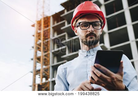 Security Inspector With Tablet In Hand On Onstruction Site. Businessman Builder Looks Into Industria