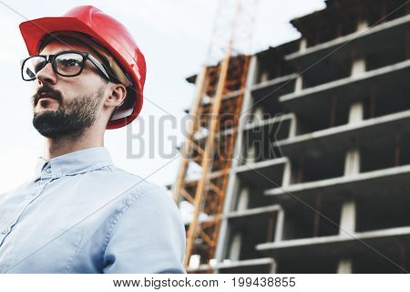 Portrait Of Modern Engineer Or Safety Inspector In Red Hard Hat And Glasses At Construction Site Of