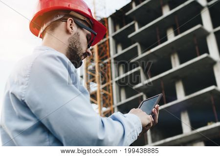 Bearded engineer in red hard hat with modern industrial electronic tablet on background of reinforced concrete skeleton of skyscraper. Close-up portrait of modern architect at work with gadget on construction site