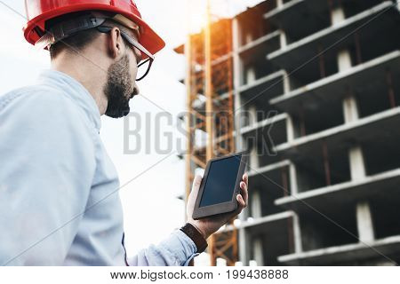 Professional Male Engineer With Modern Tablet On Construction Site. Modern Engineer Builder Checks O
