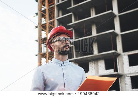 Young And Modern Engineer Builder Holds Folder With Drawings On Background Of Building Construction.