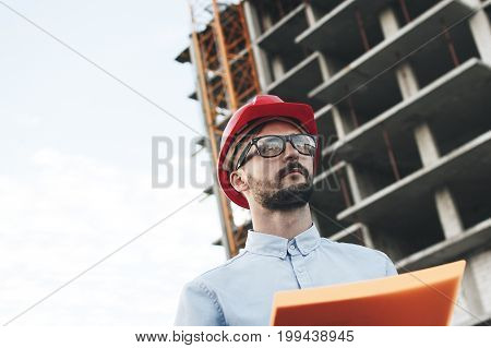 Engineer Builder In Red Helmet With Package Of Documents For Construction Of Building. Architect Or