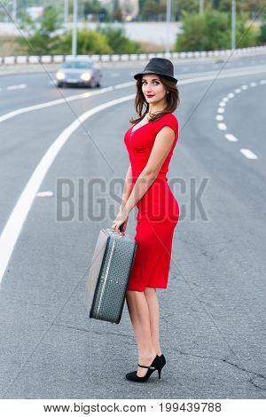 Beautiful young girl in a red dress and wearing a hat with a vintage suitcase on the roadway