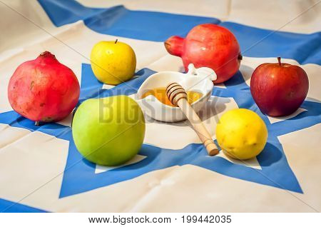 Fresh fruit: apples, pomegranates and lemons with honey during Jewish holiday Rosh HaShanah (Jewish New Year) concept. Flag of Israel background.