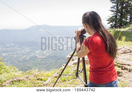 Traveller looking the nature from the high mountain with spotting scope. Tourist at the spring binoculars tripod spotting scope at the mountains looking the landscape