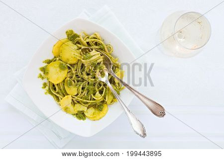 Linguine pasta with pesto genovese potatoes and white wine glass seen from above