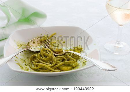 Closeup of eaten linguine pasta with pesto genovese potatoes and white wine glass