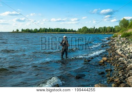 Fisherman In Water Catching Fish At Stone Shore