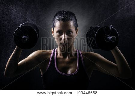 Sport young woman with dumbells on dark background