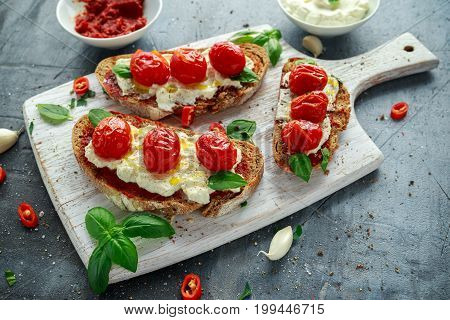 Tomato Ricotta Bruschetta with sun dried tomatoes paste, olive oil brown bread and basil in a white wooden board