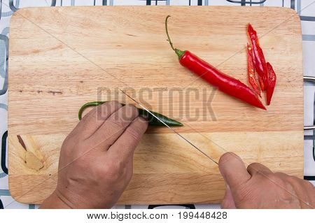 Hand cutting Hot Chili Peppers on wooden broad / Cooking green curry concept