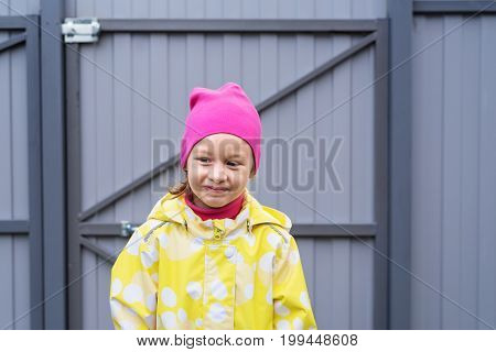 Portrait of a cute little girl in a yellow raincoat and a pink hat with a funny smile standing in frount of a grey metal door outdoors.