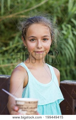 Little girl with the corn in grains at the carton cup