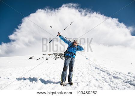 Backpacker in the mountains pretends that he shoots a bow using the example of sticks for Scandinavian walking against the backdrop of an impending storm cloud moving from the top of the mountain.