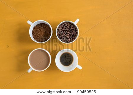 Four different cups on a yellow background. First with coffee beans, second with ground coffee, third with milk coffee and forth with just drunk coffee. Shot overhead.