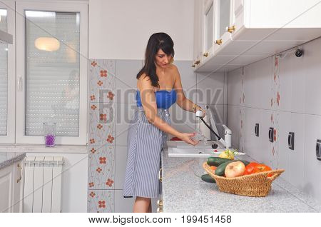 Woman washing dishes in kitchen sink. Housewife washing dishes every day