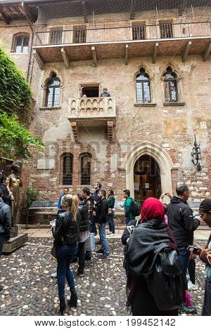 VERONA ITALY - MAY 1 2016: Tourists below the balcony in the Casa di Giulietta (Juliet's House) Via Cappello Verona Italy