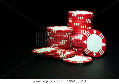 Stacks of red casino poker chips over black background
