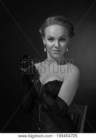 Young Beautiful Woman In Black Corset With Pearl Earrings.