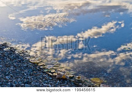Reflection of a sky with clouds on a lake beach surface in Belgrade, Serbia