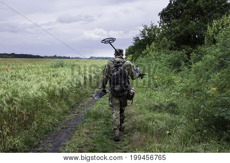 Man waking with metal detector thru the fields, soldier with metalfinder