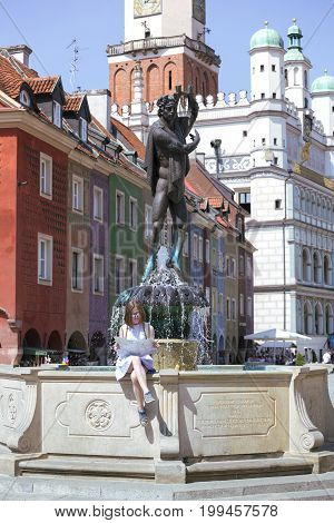 Girl Looking At The Map Sitting By The Fountain At The Main Square Rynek Of Poznan