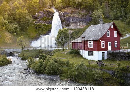 Traditional Norwegian Red Wooden House And Steinsdalsfossen